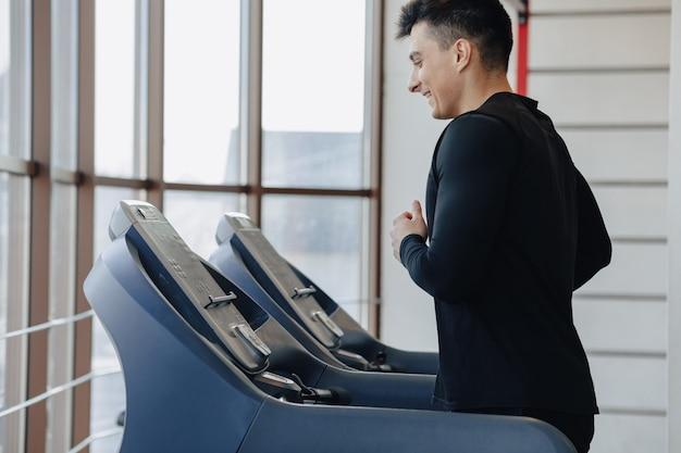 Cara elegante no ginásio está treinando na esteira. estilo de vida saudável.