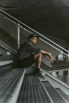 Cara elegante preto sentado na arquibancada