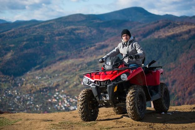 Cara em roupas de inverno em uma moto-quatro vermelha no topo de uma montanha olhando para a câmera