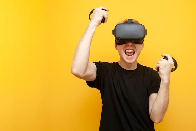 Cara emocional com óculos de realidade virtual ganha um jogo virtual, um jogador se alegra com a vitória sobre um fundo amarelo