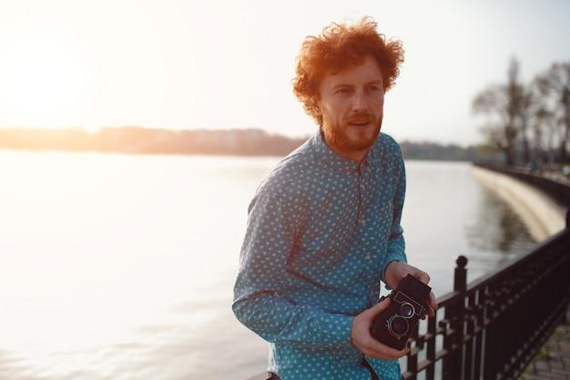 Cara encaracolado, segurando uma câmera de filme de médio formato nas mãos perto do lago