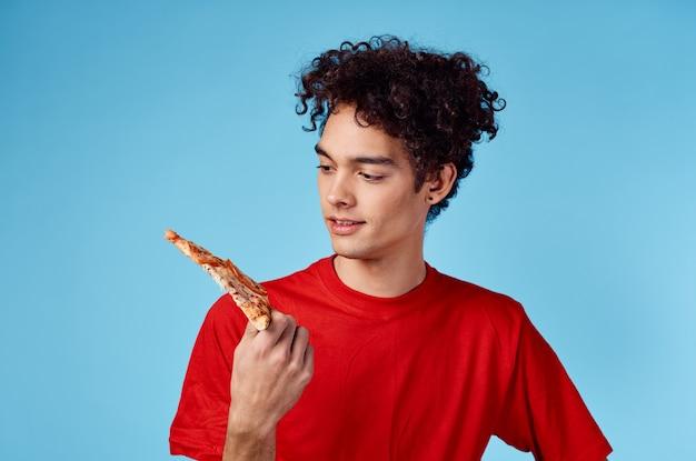 Cara enérgico com uma fatia de pizza se divertindo em um fundo azul e uma camiseta vermelha