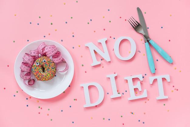 Cara engraçada abstrata de mulher de donut com olhos e cabelo da fita de centímetro no prato, talheres e texto sem dieta