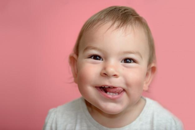 Cara engraçada da criança do bebê do divertimento feliz que sorri mostrando os dentes e o tounge, no fundo cor-de-rosa