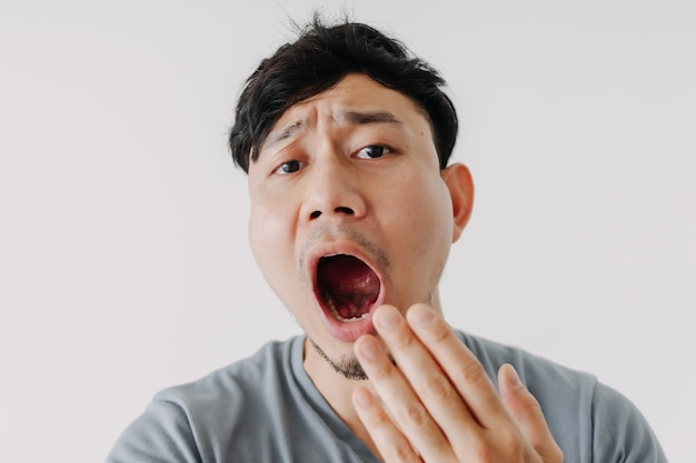 Cara engraçada de homem bocejando isolada no fundo branco