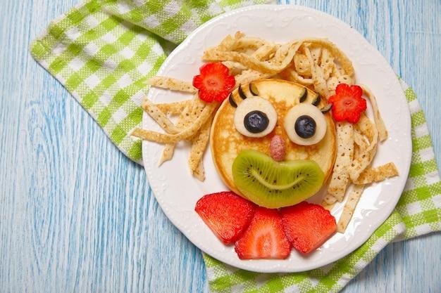 Cara engraçada de panqueca com frutas e bagas