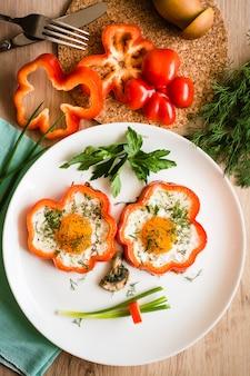Cara engraçada feita de ovos fritos, pimentão, cebola e cogumelos em um prato