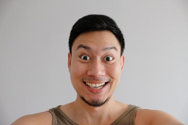 Cara engraçada feliz do sorriso do homem que toma a foto do selfie dele mesmo.