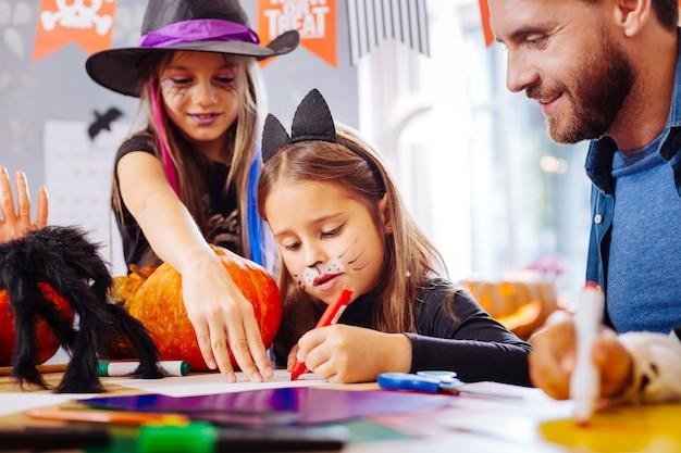 Cara engraçada. menina fofa vestindo fantasia de halloween de gato com um rosto engraçado pintado enquanto pinta fotos