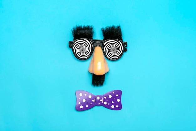Cara engraçada - óculos falsos, nariz e bigode, confetes, lantejoulas sobre fundo azul.