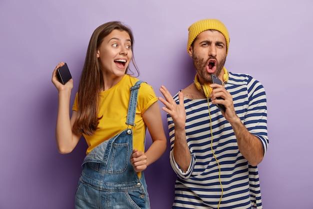 Cara engraçado canta a música favorita, segura o celular perto da boca como se fosse um microfone, mulher animada dança perto, divirta-se na festa, vista roupas da moda, tenha expressões alegres