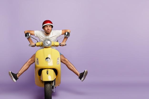 Cara engraçado com capacete dirigindo uma scooter amarela