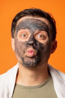 Cara engraçado com uma máscara cosmética no rosto e uma toalha laranja