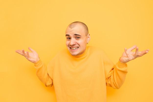 Cara engraçado confuso com uma camisola amarela, de pé sobre uma laranja