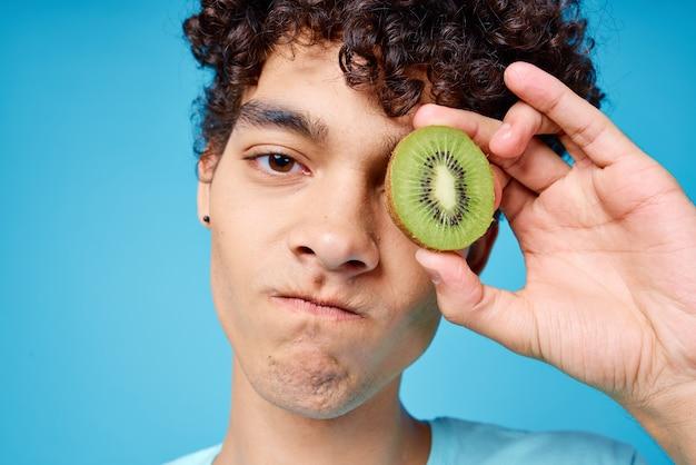 Cara engraçado e cacheado com kiwi nas mãos frutas emoções