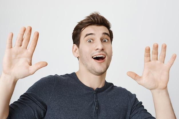 Cara engraçado surpreso levantando as mãos em sinal de rendição