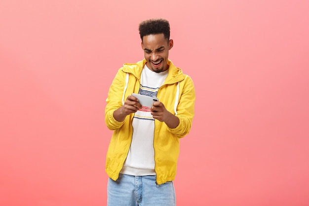 Cara entusiasmado se divertindo jogando um jogo incrível para smartphone segurando o celular com as duas mãos, olhando para a tela do dispositivo com paixão e emoção, passando o tempo livre na internet sobre o fundo rosa