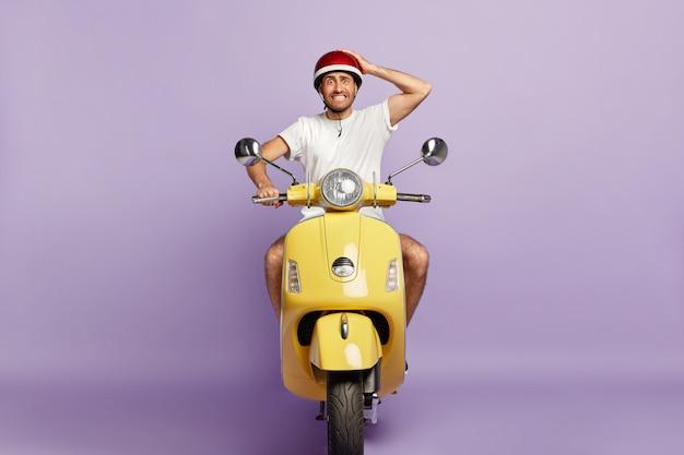Cara envergonhado com capacete dirigindo uma scooter amarela