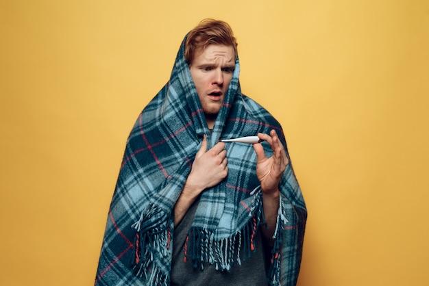 Cara envolto em manta com termômetro