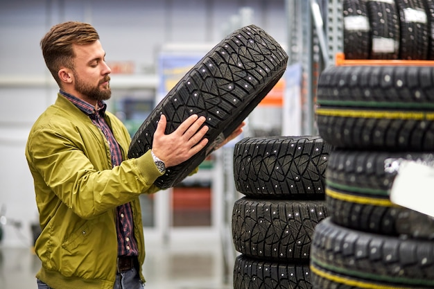 Cara escolhendo pneu de carro na loja, homem caucasiano quer comprar rodas para automóvel, examine o sortimento