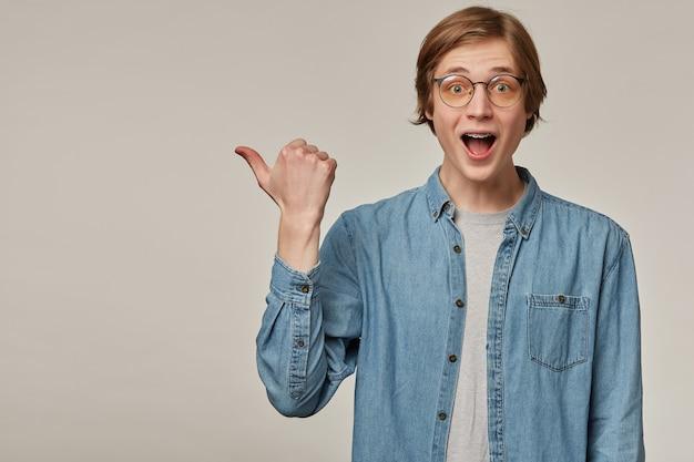 Cara espantado, homem de aparência feliz com cabelo loiro. vestindo camisa jeans azul, óculos e suspensório. apontando o polegar para a esquerda no espaço da cópia, isolado sobre a parede cinza