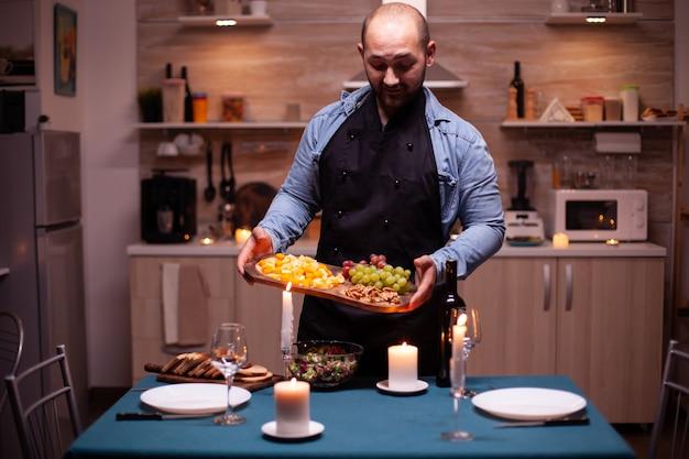 Cara esperando esposa para um jantar romântico na cozinha com comida de festa. homem preparando um jantar festivo com comida saudável, cozinhando um jantar romântico para sua mulher,