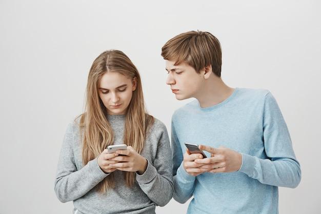 Cara, espreitar o telefone de meninas com cara séria. irmãos de mensagens no smartphone