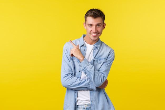 Cara esquisito bonito atrevido e elegante em camisa jeans, comprando para as férias de verão, escolhendo roupas na loja, apontando o canto superior esquerdo, demonstrando o link para a loja online, fundo amarelo.