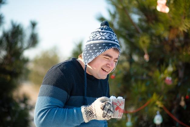 Cara está bebendo uma bebida quente com marshmallows no inverno na floresta