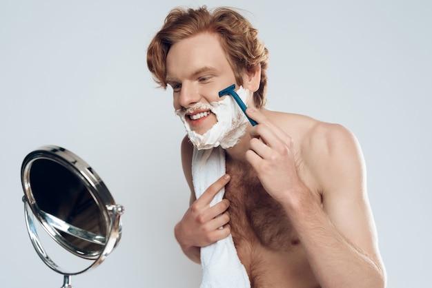 Cara está fazendo a barba com navalha, olhando no espelho. beleza masculina.