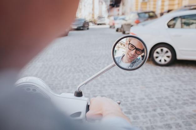 Cara está olhando no espelho pequeno na motocicleta