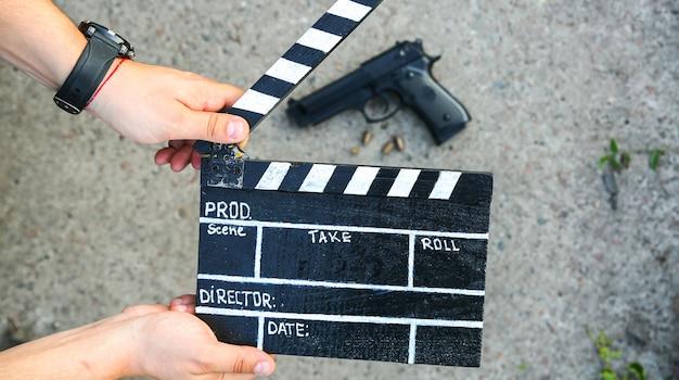 Cara está segurando uma claquete preta nas mãos. o homem está dirigindo e filmando algum filme de cinema amador. história de detetive criminal. arma no chão.