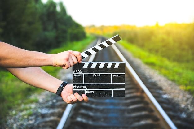 Cara está segurando uma claquete preta nas mãos. o homem está dirigindo e filmando algum filme de cinema amador. trilhas ferroviárias no fundo, conceito de viagens.