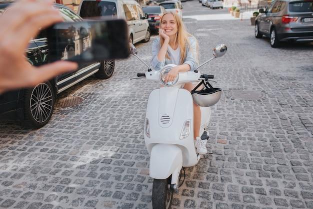 Cara está tirando foto de mulher no capacete, sentado na motocicleta