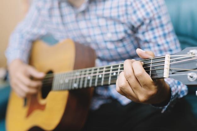 Cara estiloso e moderno. guitarra acústica tocando com a mão