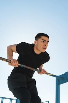 Cara europeu 20 anos em um agasalho preto fazendo acrobacias na barra de ginástica horizontal durante um treino matinal à beira-mar