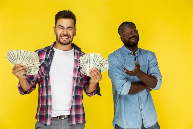 Cara europeu com grande quantidade de dinheiro em ambas as mãos e cara afro-americana não está tendo nada