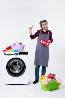 Cara exultante de avental segurando uma placa de venda em pé perto da máquina de lavar roupa no fundo branco.