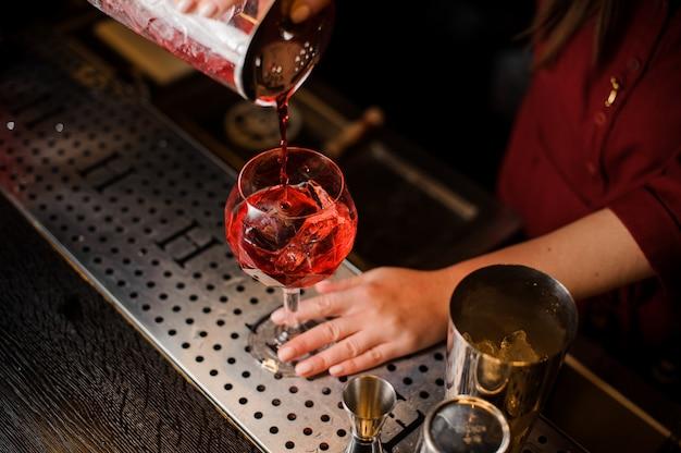 Cara fazendo um cocktail campari no bar