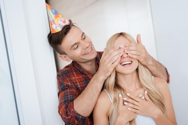 Cara fechou as mãos de olhos de menina. sorrisos da menina do aniversário.