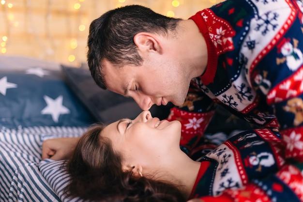 Cara fechou os olhos e quer beijar a garota garota fechou os olhos e sorri eles deitam na cama