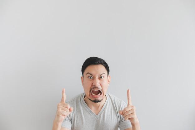 Cara feia do homem em t-shirt cinza com ponto de mão no espaço vazio.