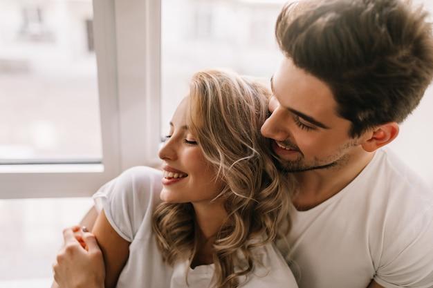 Cara feliz, abraçando a namorada de manhã. retrato interior de mulher loira relaxada, relaxando com o namorado.