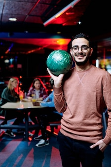 Cara feliz com bola verde jogando boliche no centro de lazer em um bar e os amigos sentados à mesa tomando drinks