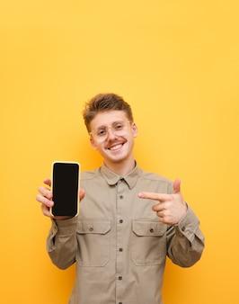 Cara feliz de camisa e óculos está apontando o dedo para smartphone com tela preta