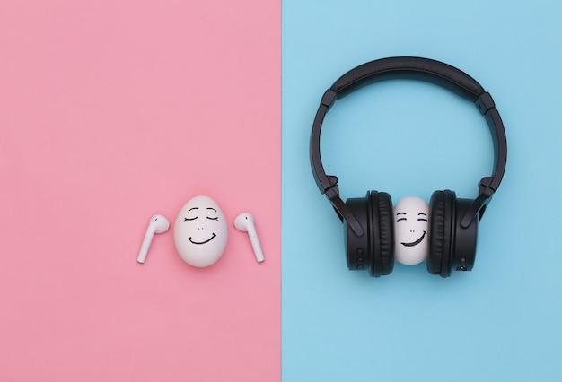 Cara feliz de dois ovos ouve música com fones de ouvido sem fio em um fundo rosa azul.