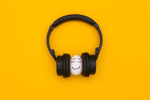 Cara feliz de ovo de galinha com fones de ouvido em fundo amarelo.