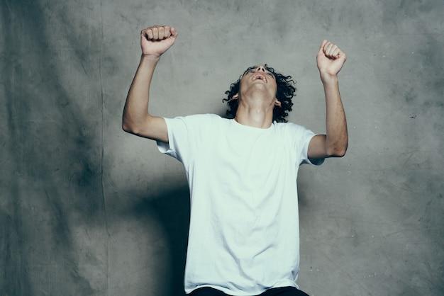 Cara feliz e cacheado com uma camiseta gesticulando com as mãos em uma sessão de fotos de parede de tecido