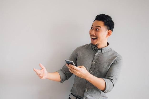 Cara feliz e uau do smartphone asiático do uso do homem no fundo cinzento isolado.