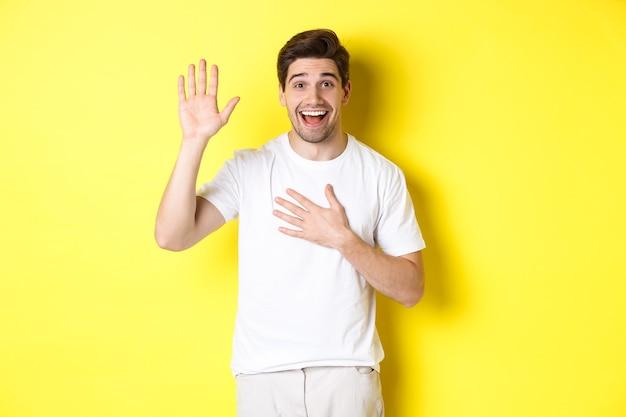 Cara feliz fazendo promessa, segurando a mão no coração, jurando dizer a verdade, em pé sobre uma parede amarela em uma camiseta branca.